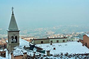 Снег на крышах домов в Римини зимой